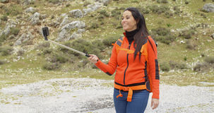 Young woman hiker using a selfie stick Stock Images