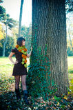 Young woman hiking in autumn park dressed in knitted dress. Royalty Free Stock Photography