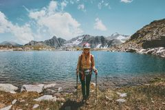 Young Woman hiking at blue lake in mountains Travel Lifestyle adventure concept summer vacations outdoor exploring. Wild nature wearing helmet Royalty Free Stock Photos