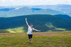 Young woman Hiking at Carpathians Mountains stands on top of a hill stock image
