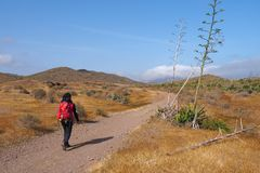 Young woman hiking in dry, desert-like Cabo di Gata Nature Park.
