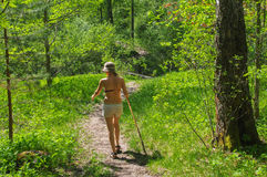 Young woman hiking through green forest path with a walking stick. A young woman hiking through green forest path with a walking stick stock images
