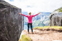 Young woman hiking on kjerag. Happy girl enjoy beautiful lake and good weather in Norway royalty free stock image