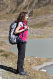 Young woman hiking in nature watching lake landscape. Woman on a hiking trip on the Swiss alps enjoying lake view Royalty Free Stock Photo