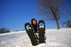 Young woman hiking with snowshoes / Rackets royalty free stock photo
