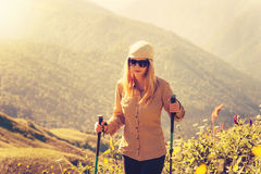 Young Woman hiking with trekking poles Travel Lifestyle concept Stock Photos