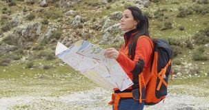 Young woman hiking using a map stock footage