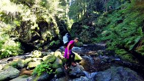 Young woman hiking by a waterfall stock video footage