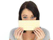 Young Woman Hinding Behind White Chocolate Bar Royalty Free Stock Photography