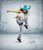 Young woman hip hop dancer. With grunge wall background texture royalty free stock photo