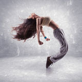 Young woman hip hop dancer. With grunge wall background texture stock images