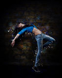 Young woman hip hop dancer. With grunge wall background texture stock photos