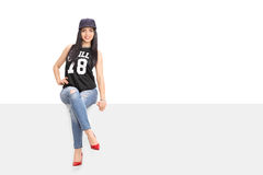 Young woman in hip hop outfit sitting on a billboard Stock Image