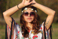 Young woman in hippie style looking at the camera and holding hands on head Outdoors Stock Images