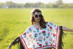 Young woman hippie in sunglasses standing outdoors arms outstretched Outdoors Royalty Free Stock Photos
