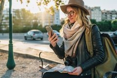 Young woman, hipster girl tourist with backpack and camera sits on bench in city street, uses smartphone, holding map. Young woman tourist, hipster girl with Royalty Free Stock Photo