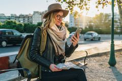 Young woman, hipster girl tourist with backpack and camera sits on bench in city street, uses smartphone, holding map. Young woman tourist, hipster girl with Royalty Free Stock Image