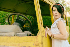 Young woman hipster tries to steal old retro car bus but is afra Royalty Free Stock Photos
