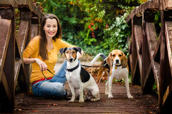 Young woman and his dogs. Young girl in yellow shirt. Holding two cute dog on a wooden bridge Royalty Free Stock Photo