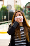 Young woman with his hand over the protective mask on the street in the city with air pollution, city background Stock Image