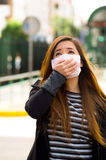 Young woman with his hand over the protective mask on the street in the city with air pollution, city background Stock Photo