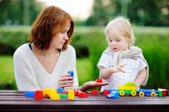 Young woman with his son playing with plastic blocks Stock Photos