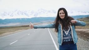 Young woman hitch-hiking on a road at the fields. Young girl hippy hitchhiking on the road. Among the mountains in. Nature. Going on the road stock video footage