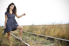 Young woman hitch-hiking train on the railroad Royalty Free Stock Image