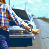 Young woman hitch-hiking. On a road at the fields Stock Photo