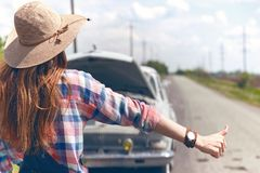 Young woman hitch-hiking. On a road at the fields Royalty Free Stock Image