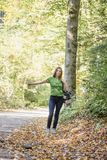 Young woman hitchhiker standing in autumn forest. Young woman hitchhiker standing on the side of the road in autumn forest, thumbing for picking her up Royalty Free Stock Photography