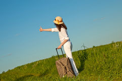 Young woman hitchhiking. Standing on a rural road with a suitcase Royalty Free Stock Image