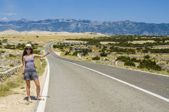 Young woman hitchhiking along empty road Stock Photos