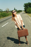 Young woman hitchhiking along a road. Stock Photo