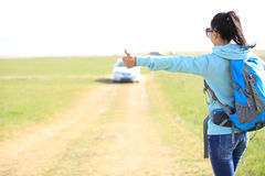 Young woman hitchhiking along a road. Stock Photos