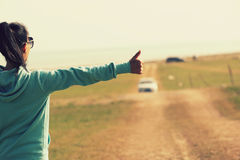 Young woman hitchhiking along a road. Royalty Free Stock Image