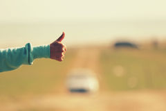 Young woman hitchhiking along a road. Royalty Free Stock Images