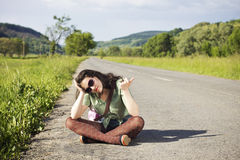 Young woman hitchhiking, being bored Royalty Free Stock Images