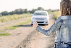 Young woman hitchhiking in the countryside Stock Image