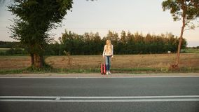 Young lady hitchhiking on countryside road. Young woman hitchhiking on countryside road. Young female with red suitcase standing on roadside and hitchhiking stock video