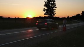 Young woman hitchhiking on countryside road. Young female with red suitcase standing on roadside and hitchhiking while travelling through countryside. Slow stock footage