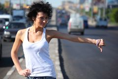 Young woman hitchhiking on highway Royalty Free Stock Photos