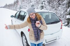 Young woman hitchhiking on the snow-covered winter road. She stands next the car. Snowy weather. Woman holds the phone in her hands and smiling. She looks at Stock Photos