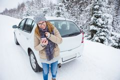 Young woman hitchhiking on the snow-covered winter road. She stands next the car. Snowy weather. Woman holds the phone in her hands and smiling. She looks at Stock Photo