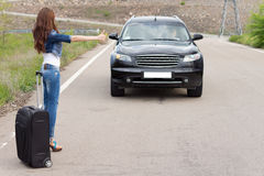 Young woman hitchhiking with a suitcase. Young women hitchhiking with a suitcase on a rural road flagging down an approaching car with her thumb as she solicits Royalty Free Stock Photos
