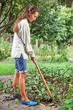 Young woman with hoe working in the garden. Bed Royalty Free Stock Photo