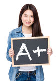 Young woman hold with chalkboard showing A plus mark Stock Photography