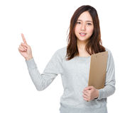 Young woman hold with clipboard and finger point up Stock Photo