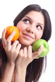 Young woman hold fruit - apple and orange. Royalty Free Stock Image