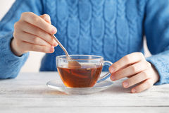 Young woman hold glass cup oа tea on table Stock Photos